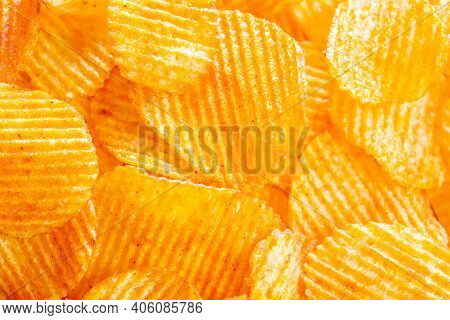 Background Of Yellow Golden Grooved Fried Potato Chips With Bright Lit