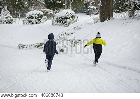 Children Play In Winter. Two Boys, Brothers, Running Outside In The Snow. Small Children Play In The