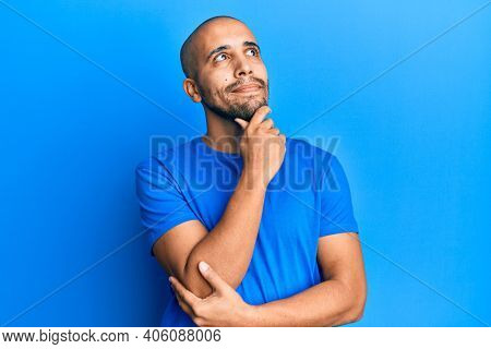 Hispanic adult man wearing casual blue t shirt thinking concentrated about doubt with finger on chin and looking up wondering