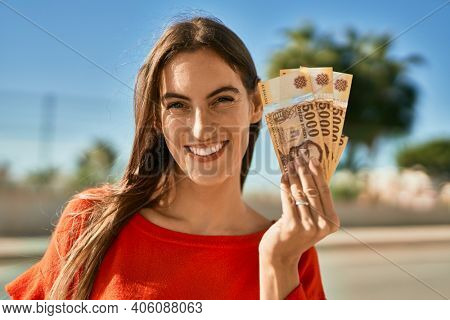 Young hispanic woman smiling happy holding hungarian forint banknotes at the city.
