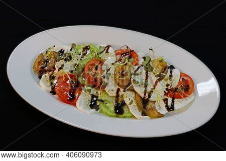 Heirloom Tomatoes And Mozzarella Salad In A White Plater With Black Background