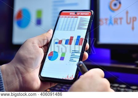 Businessman Hand Holding Cellphone With Business Report. Business And Financial Success Concept. Clo