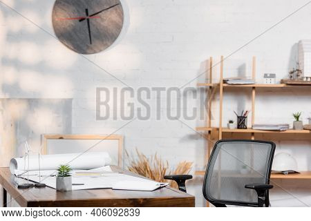 Desk With Blueprints And Wind Turbines Models In Architectural Bureau