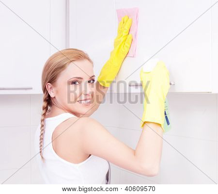 beautiful  young housewife wearing gloves cleaning the furniture  in the kitchen at home