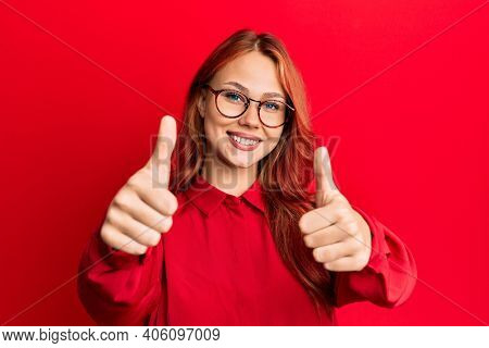 Young beautiful redhead woman wearing casual clothes and glasses over red background approving doing positive gesture with hand, thumbs up smiling and happy for success. winner gesture.