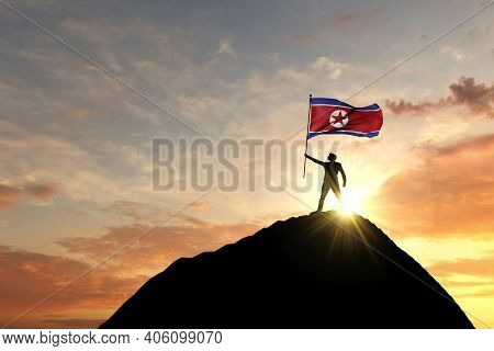 North Korea Flag Being Waved At The Top Of A Mountain Summit. 3d Rendering