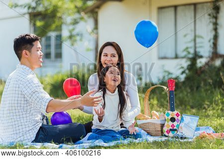 Happy Asian Young Family Father, Mother And Child Little Girl Having Fun And Enjoying Outdoor Sittin