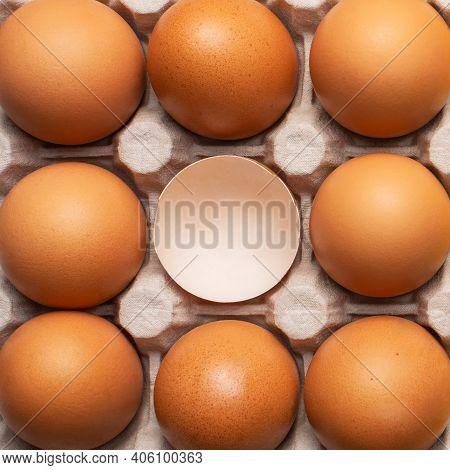 Brown Fresh Chicken Eggs And One Broken Eggshell In Carton Box. Closeup Natural Organic Egg Pattern.