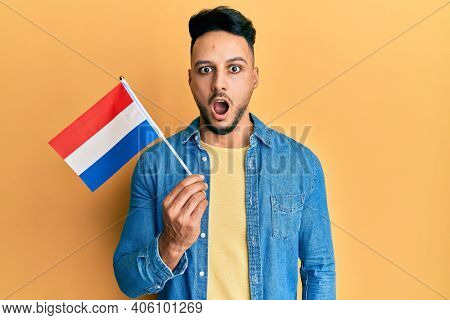 Young arab man holding holland flag scared and amazed with open mouth for surprise, disbelief face