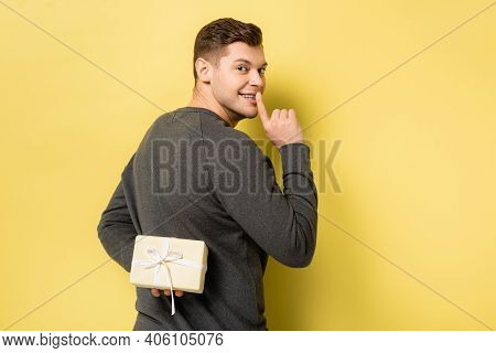 Back View Of Man Showing Shh Gesture And Hiding Present On Yellow Background