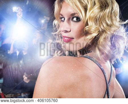 Portrait of beautiful woman posing while being photographed by paparazzi