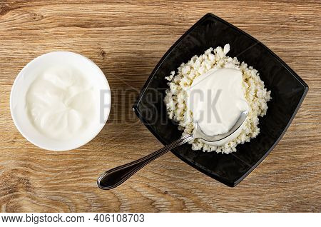 White Bowl With Sour Cream, Spoon In Black Glass Bowl With Defatted Grainy Cottage Cheese And Sour C
