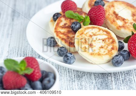 Close Up Of Cottage Cheese Pancakes With Fresh Berries On White Wooden Table. Tasty Breakfast Food.