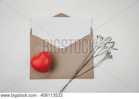 Blank White Paper Is Placed On Open Brown Paper Envelope With Red Heart With Limonium Dry Flower On
