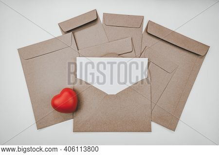 Blank White Paper Is Placed On The Open Brown Paper Envelope With Red Heart. Horizontal Blank Greeti