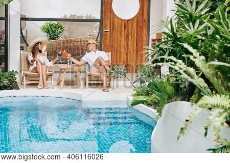 Happy Couple Relaxing In Chaise-lounges By Swimming Pool And Enjoying Delicious Fruit Cocktails