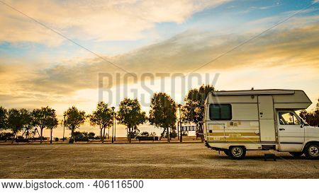 Camping On Sea Shore. Old Camper Car With Alcove On Beach At Evening.