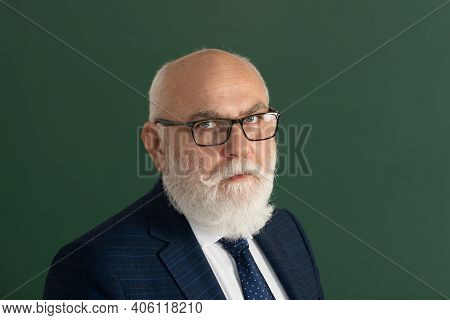 Serious Teacher. Closeup Portrait Of Senior Academic Professor Near Empty Blackboard. Knowledge And