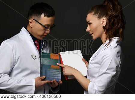 Young Woman And Man Doctors In White Medical Uniform Gown Discuss Professional Books With Blank Cove