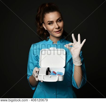 Young Woman Doctor Nurse In Blue Uniform And Protective Latex Gloves Holding First Aid Kit In Hands