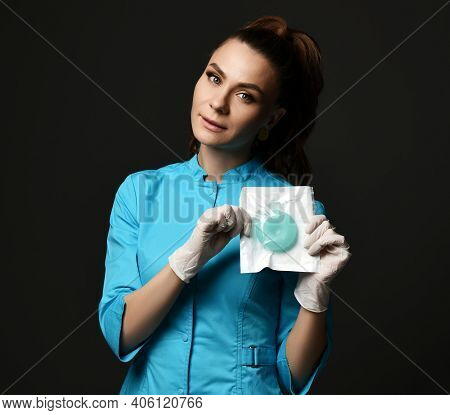 Young Woman Doctor Nurse In Blue Uniform And Protective Latex Gloves Demonstrates Special Medical To
