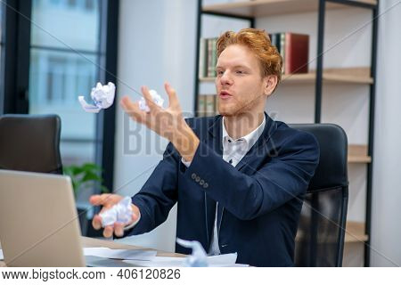 Young Man Juggling With Crumpled Paper In Office