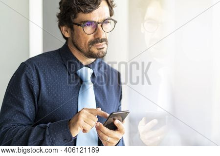 Business Man Wearing Glasses Looking Through Window Holding His Smartphone. Successful Male Portrait