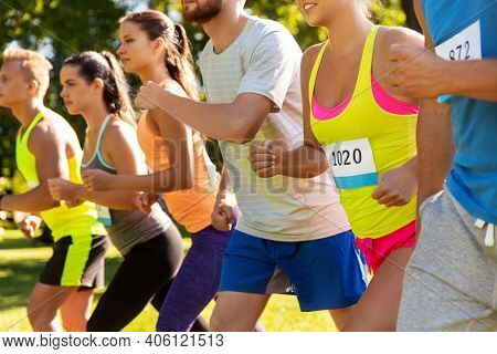 fitness, sport, race and healthy lifestyle concept - group of friends or sportsmen with badge numbers on start of running marathon outdoors