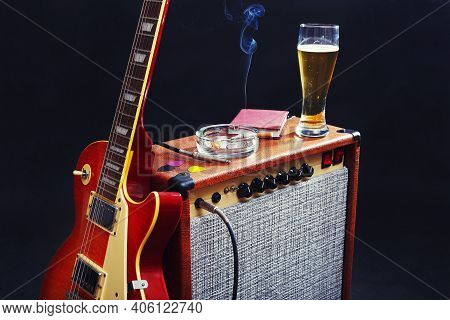 Combo Amplifier For Electric Guitar With Guitar, Glass Of Beer And Smoking Cigarette On The Black Ba