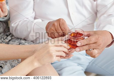 Close-up Image Of Adult Daughter Giving Small Cup Of Black Tea To Senior Father Visiting Her Family