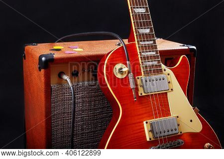 Combo Amplifier For Electric Guitar With Guitar On The Black Background.