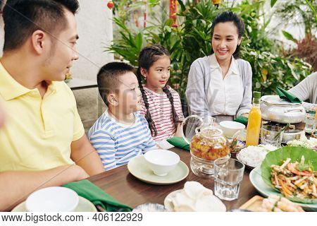 Cute Little Boy Reciting Poem For Family When Sitting At Big Dinner Table Outdoors