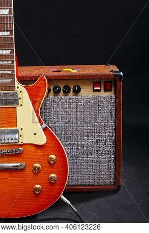 Amplifier For Guitar With Honey Sunburst Guitar On The Black Background.