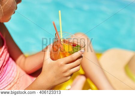 Little Girl Relaxing In Swimming Pool, Enjoying Suntans, Drink A Juice On Inflatable Yellow Mattress
