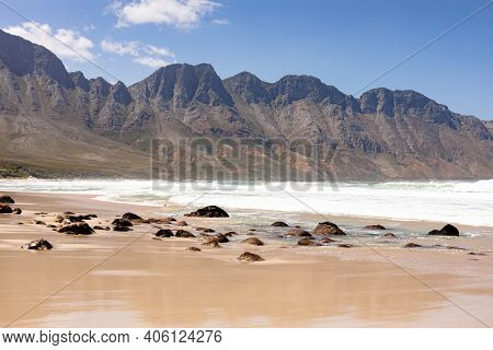 Beautiful beach by the sea and mountains with rocks and golden sand on a sunny day. beautiful view of sunny coast