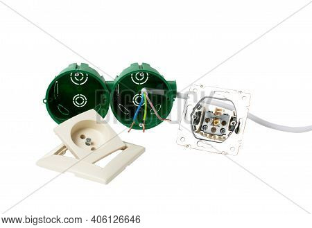 On A White Table, A Disassembled Electrical Outlet, Ready To Install, Stripped Wires And A Red Screw