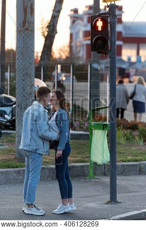 Couple In Love Met Stands At Traffic Light And Hugs. Young Lovers.