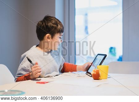 Authentic Portrait Of Preschool Kid Using Tablet For His Homework, New Normal Life Child Boy Use Tou