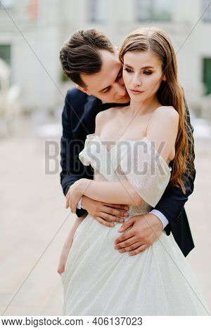 Beautiful, Gentle And Happy Bride And Groom. Man Gently Kisses Womans Face
