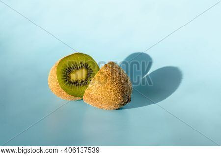 Halves Of One Kiwi With A Shadow In The Form Of A Heart On A Blue Background. Minimalism St. Valenti