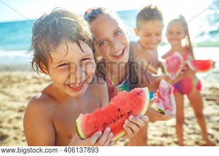 A Group Of Children Have Fun Playing At The Sea. Children In Bathing Suits. Friends Holding Hands An
