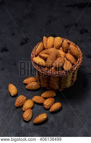Almonds On A Black Background. Isolated Almonds. Roasted Almonds In A Small Basket