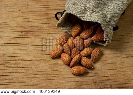 Almonds On A Wooden Background. Isolated Almonds. Roasted Almonds Pouring Out Of The Bag