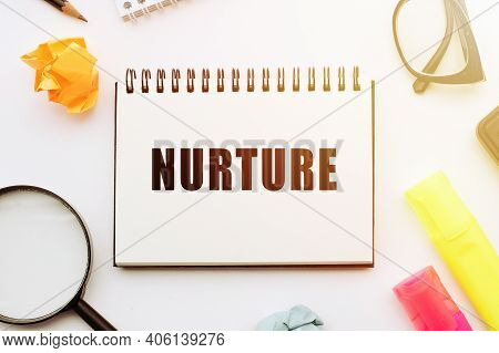 Text Nurture In Notebook On White Table With Office Tools.