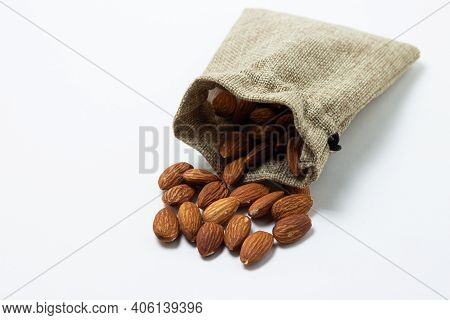 Almonds On A White Background. Isolated Almonds. Roasted Almonds Spilled Out Of The Bag