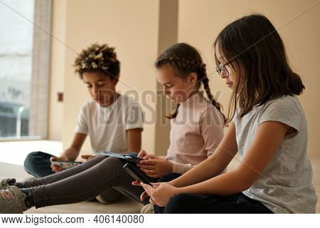 Three Multi Ethnic African, Caucasian And Korean Little Kids Sit Indoor Using Wireless Gadgets. Over