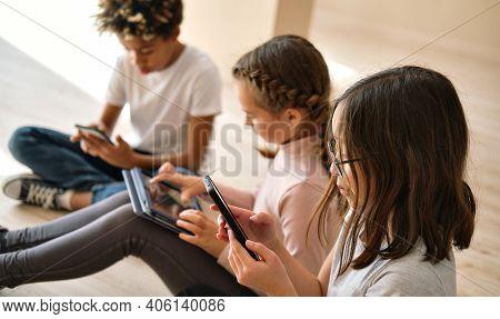 Three Multi Ethnic African, Caucasian And Korean Little Kids Sit Indoor Using Diverse Wireless Gadge