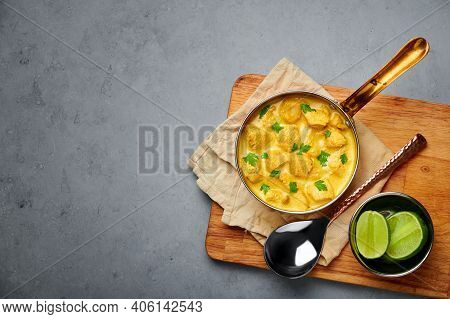 Chicken Korma In Copper Pan On Gray Concrete Table Top. Indian Cuisine Meat Curry Dish With Coconut