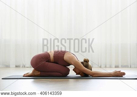 Young Woman Practicing Extended Child Asana In Yoga Studio. Utthita Balasana Pose