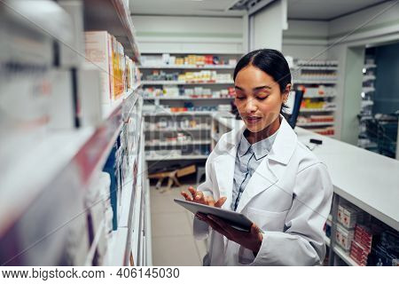 Young Female Pharmacist Checking Inventory Of Medicines In Pharmacy Using Digital Tablet Wearing Lab